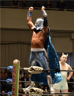 A color photograph of a Japanese wrestler wearing a light blue mask, cape and trunks posing on a turnbuckle with his hands in the air