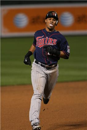 A man in a blue baseball jersey, gray pinstriped pants, a batting helmet, and black gloves runs the bases.