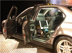 Side view of a vehicle with its doors open. Behind the left front seat can be seen a steering wheel and monitor.