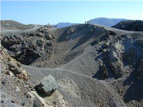 Small figures of people can be seen at the top looking into craters strewn with grey rocks.