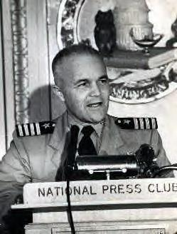 Middle-aged man wearing U.S. Navy khaki uniform and Captain shoulder epaulettes standing behind a lectern with microphone and placard that reads