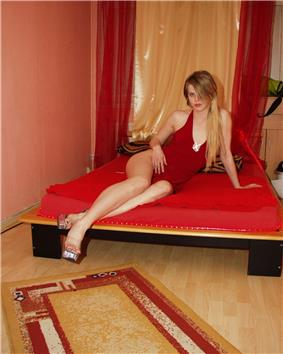 woman with long, blond hair in a red, one-piece lingerie lounging on a small bed in a small room