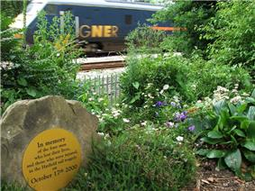 An  passing the memorial garden created next to the  for the four people who died in the Hatfield rail crash