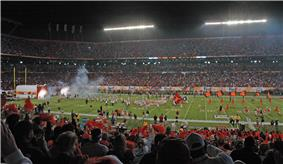 Distant figures rush onto a darkened football field carrying orange flags. In the foreground are the heads of spectators.