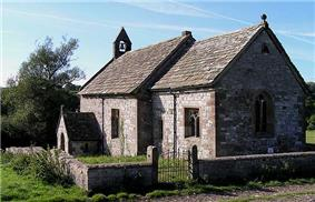 A simple stone church with a bellcote, seen from the southeast
