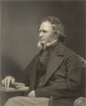 A stately-looking gentleman in a dark suit, sitting with a book