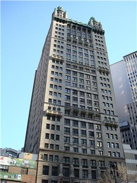 Ground-level view of a 30-story building with a tan exterior and a square cross-section; spires sit atop the roof of the building at each corner