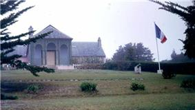 Photo of a front garden and large brown building. French flag on a flagpole next to a small cannon.