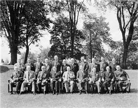 A posed group of men, taken out of doors, with one row seated, one standing