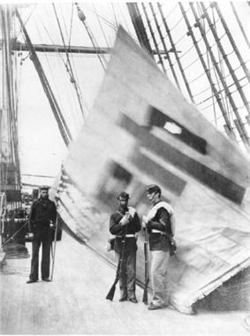 two Marines stand in front of and one sailor next to a white flag with a Chinese character, displayed from the rigging of a ship