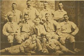 A baseball team is posing for a photograph. There are four men standing, five men sitting, and two men are laying on the ground.