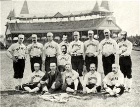 Two rows of men: one row standing behind a second row seated on the ground. The men are wearing white baseball uniforms with