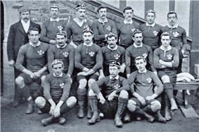 Three rows of rugby players wearing their playing uniforms and caps