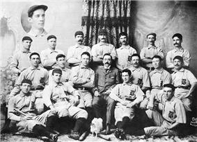 Three rows of men in white baseball uniforms and dark caps; the rear row is standing, the middle row is seated (with a man in a tweed suit in the middle), and the front row is seated on the floor. The baseball uniforms have a dark Old English-style