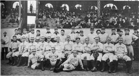 Two rows of men in white baseball uniforms. Those in the back row wear dark baseball  caps with