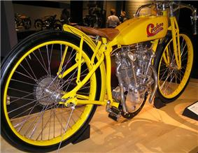 A pristine 1914 motorcycle with a bright yellow frame, racing style handlebars and skinny racing tires.