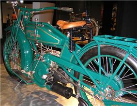 A pristine motorcycle of 1919, painted green with a v-twin engine and footboards.