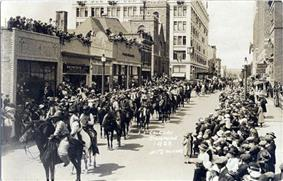Hundreds of men on horseback march down a city street as people observe from the sidewalks and rooftops.
