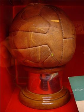 12-panel brown leather football on a plinth of hardwood, with a brass panel inscribed with the names of the victorious team members, photographed through the glass of a display case