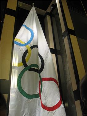 White flag hanging from the ceiling with the five interlocking rings symbolic of the Olympic Games. The rings are each a different color with blue, yellow, black, green, and red.