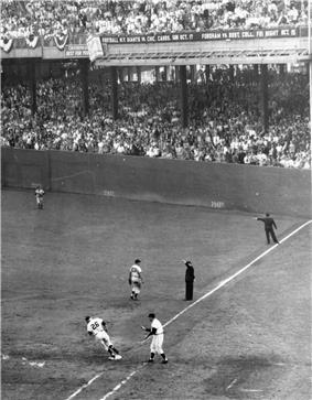 A black and white image of right field and first base in a baseball diamond in a large stadium with filled stands. A runner is rounding first.