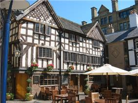A timber-framed building, three floors high with a gabled roof. There are tables and chairs outside