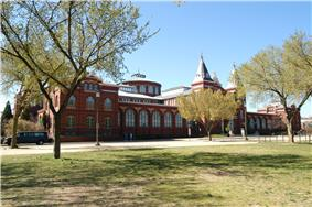 A long brick building is partial obscured by three trees. There is a central entranceway flanked by two towers, and a rotunda behind the entrance.