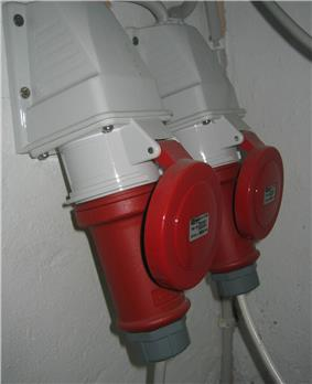 In the foreground, a downward-angled industrial wall socket with a red cap, mounted to a wall; a red plug is inserted into it. In the background, another similar connection.