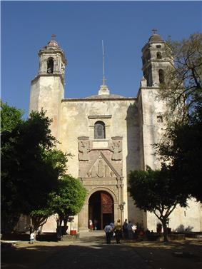 Front of a church with two towers. The portal around the door is decorated with reliefs of two angels, Maria and two other figures.