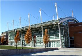 Ground-level view of a building with white poles sticking up from its sides and with trees in autumn colors in front of it