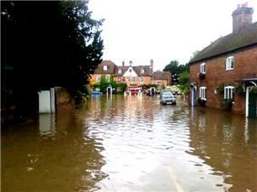 Photograph showing severe flooding to a road and housing; cars are partly submerged and fire appliances (including a dinghy) are in the distance