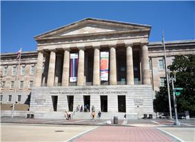 A 3 story building. The first story is granite, while the second two are sandstone. There is a pedimented front with columns spanning the second and third floors and the entrance on the first.