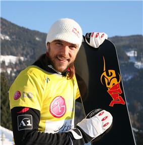 Man wearing a yellow snowboarding jersey and a white knitted cap. He is holding a black snowboard with gloved hands, and is standing on a snowy hill covered with trees.