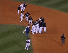 Several men in white baseball jerseys, some wearing black jackets, congregate around second base on a baseball diamond.