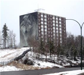 Highland Tower, chosen for the Spirit Way wolf mural, is the most prominent building on Thompson's skyline