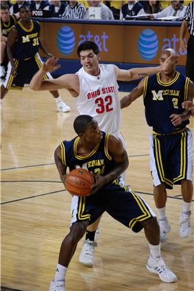 A basketball player in a dark blue uniform is maneuvering with a basketball while the defender in white is in the air behind his back.