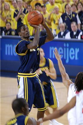 A basketball player in a dark blue uniform is shooting a jump shot over the outstretched arm of a defender in white.