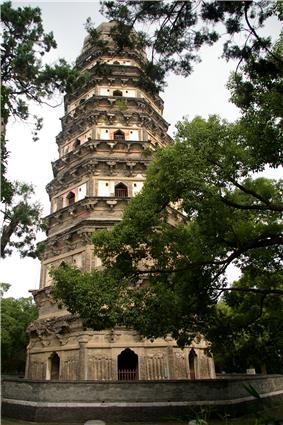 A seven-story, brick, octagonal pagoda, surrounded by trees. Each story is separated by a pair of eaves.