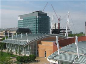 View from above of a building with white poles sticking up from its sides and the cables connecting them.  A taller building is in the background and a connected brick building is visible on its right.