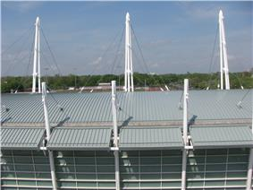 view from above of the roof of a curved roof of a building with tall white poles and various cables connecting them