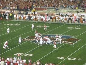 Several American football players in red and white uniforms  in action at the mid-field area of the stadium with a large logo visible on the field. Players are visible on both sidelines with the edge of the spectator stands also visible.
