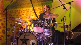 A colour photograph of Starr playing a dark coloured drum kit on a stage. The background is yellow.