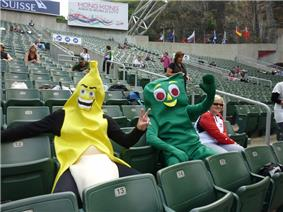 Two people dressed in fancy costume (Gumby - right; Banana – left) seated in stadium