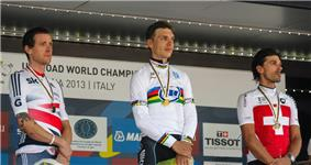 Three cyclists standings on the awards podium.