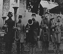 Soldiers stand in a row holding various brass instruments.