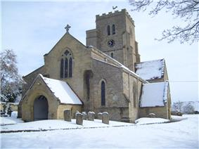 Stone building with gravestones in foreground and to the left; the church tower is surmounted by an ornamental weathercock, and has a clock showing 10.35. The roofs and surrounding areas are covered in snow.
