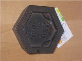A hexagonal 2kg weight – top view showing inscription