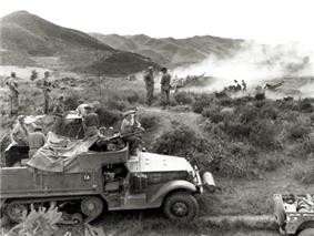 A half track vehicle sits in the foreground in a grassy open area, with a large calibre machine-gun mounted on top. Soldiers using binoculars are sitting on the vehicle, while in the background smoke obscures a number of artillery guns which are firing