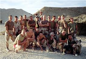 A group of Marines in desert camouflage posing outside their rest areas.