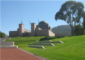 A view looking up a landscaped hill; steps lead to the entrance of a large cupola-topped building with three flag poles in front.